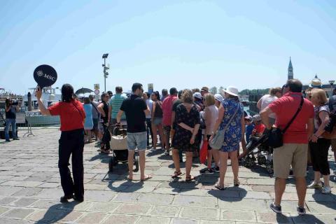 Pasajerons de MSC Opera esperan para embarcar en un bote que les llevará a su crucero en Venecia.