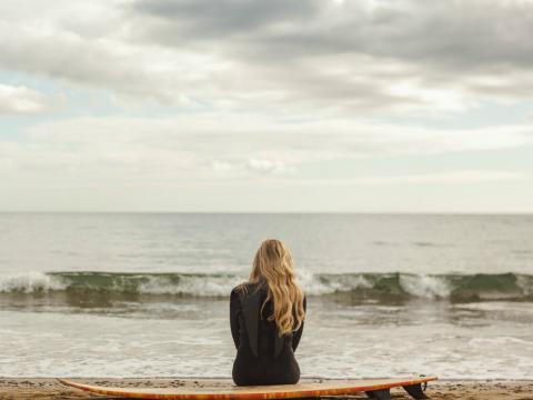 Una persona mira al horizonte desde la playa