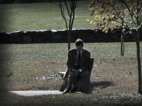 Un hombre se sienta en un banco apenado por su situación