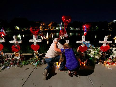 José Luis Morales llora arrodillado mientras es abrazado por una mujer frente a la cruz de su hermano Edward Sotomayor Jr., fallecido en el tiroteo de un club nocturno de Orlando, en Florida (EE. UU.), el 20 de junio de 2016.