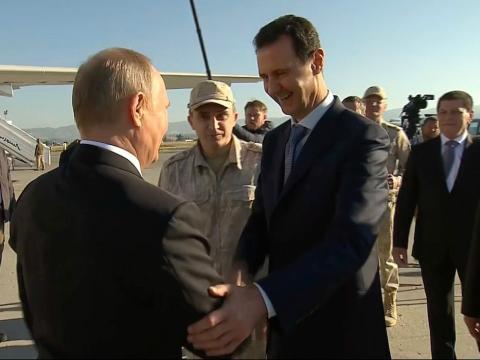 Captura de un reportaje de televisión en el que se ve (de der. a izqd.) al presidente de Siria, Bashar al-Ásad, saludando al presidente de Rusia, Vladimir Putin, en la base áerea siria de Hemeimeem el 11 de diciembre de 2017.