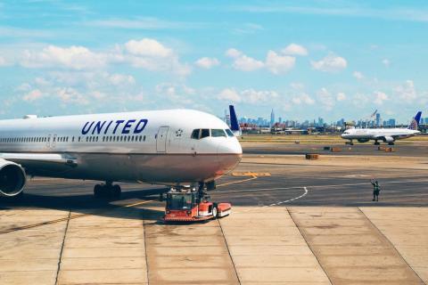 Muestra una pista de aterrizaje con un avion de United en primer plano
