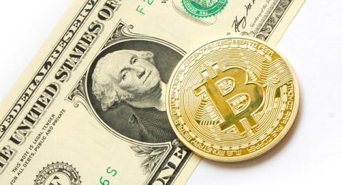 Una moneda de bitcoin junto a un billete de un dólar