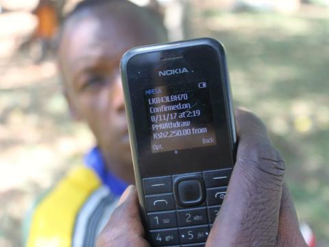 Una persona muestra un teléfono móvil Nokia en un proyecto de bancarización.