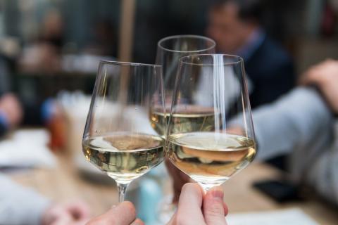 Tres personas brindan con vasos de vino blanco