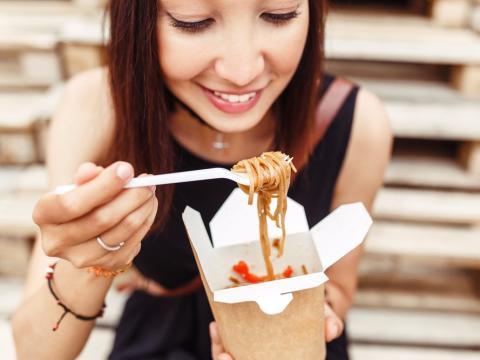 Chica comiendo comida para llevar