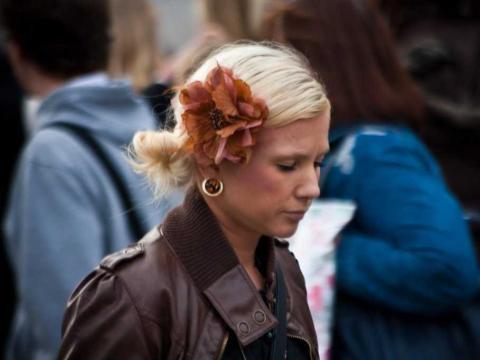 Una chica con expresión triste camina en dirección contraria al resto