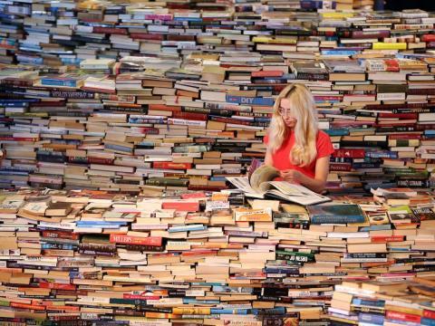 Chica leyendo rodeada de libros concepto el conocimiento no tiene límites