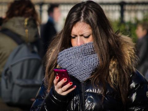 Una chica mira su smartphone con expresion seria