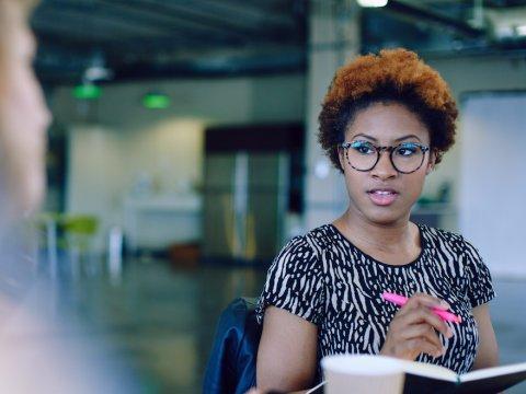 Una chica sentada frente a otra persona toma notas en su cuaderno