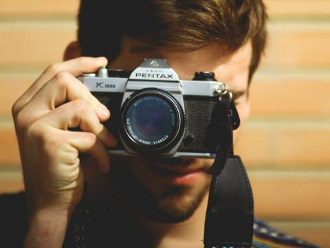 Chico saca una foto con una camara Pentax