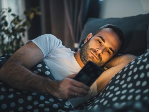 Un joven mira el teléfono tumbado en la cama