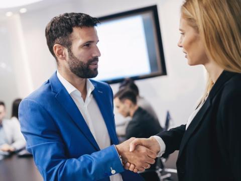 Dos personas se presentan dándose la mano en un evento de networking