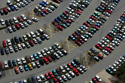 Coches aparcados al aire libre en un centro comercial.