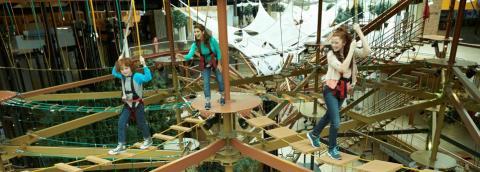 Tres niñas juegan en una carrera de obstáculos de un centro comercial.