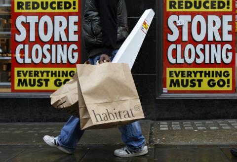 Plano detalle de una persona de compras frente a un escaparate cerrado