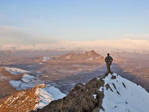 Un hombre mira el horizonte desde lo alto de una montaña