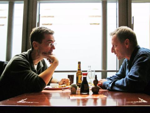 Dos hombres adultos hablan en una mesa mientras comen