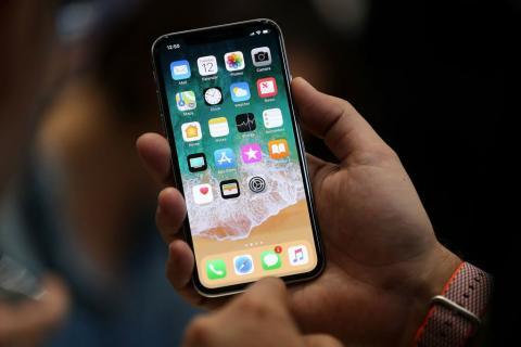Fotografía del iPhone X sostenido en una mano.
