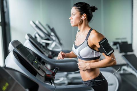 Mujer haciendo ejercicio en la cinta de correr del gimnasio