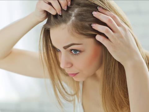 Una mujer se mira el pelo en el espejo