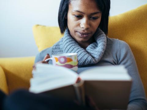 Mujer se relaja leyendo un libro bebiendo una taza de café