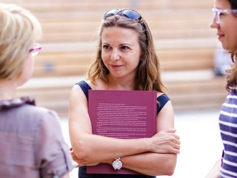 Una mujer sujeta un libro mientras mantiene una conversación con otras dos