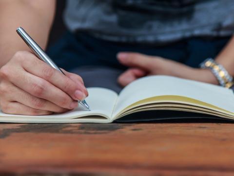 Imagen de una mano anotando algo en un cuaderno
