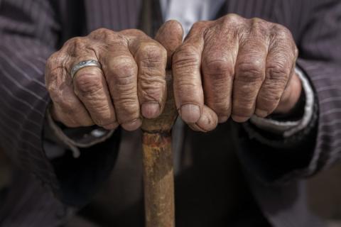 Una persona mayor sosteniendo un bastón