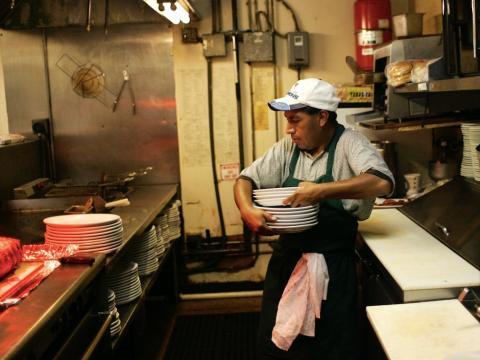 Persona de origen latino lava platatos en la cocina de un restaurante