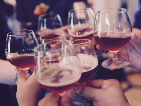 Bebidas alcoólicas: personas brindan con copas de cerveza