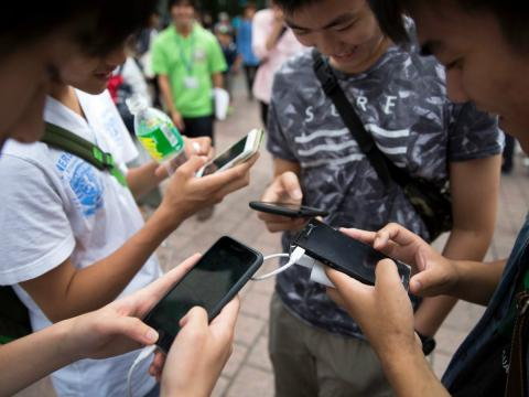 Un grupo de adolescentes utiliza el teléfono móvil