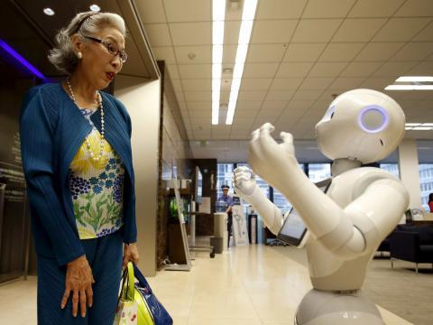 Una señora conversa en Japón con un robot