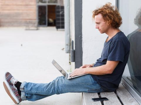 Un hombre sentado con un ordenador portátil