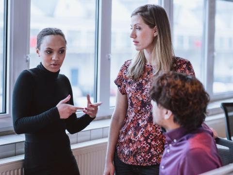Tres mujeres mantienen una conversación en un ambiente laboral
