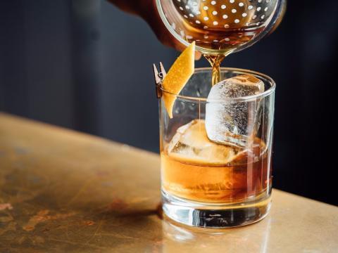 Preparan una bebida alcohólica en un vaso con hielo y naranja