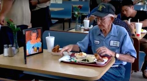 Un viudo almuerza con la fotografía de su mujer