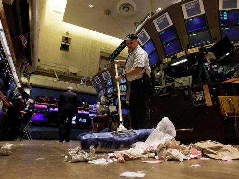 Un hombre limpia el suelo en la bolsa de Wall Street