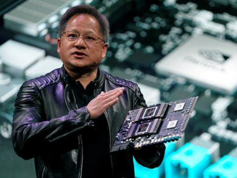El CEO de Nvidia, Jensen Huang, muestra la placa base de su robotaxi Drive Pegasus durante su intervención en la feria CES de 2018.