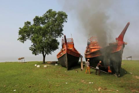 Trabajadores cerca de Calcuta reparan unos barcos