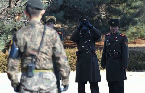 Dos soldados norcoreanos observan a un soldado surcoreano.
