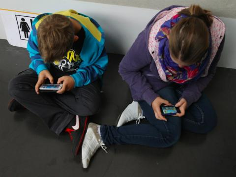 Dos niños usan su móvil