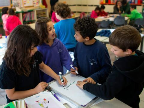 Un grupo de niños habla en clase mientras realizan sus tareas.