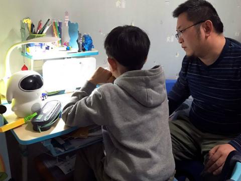 Un niño hace los deberes junto a su padre