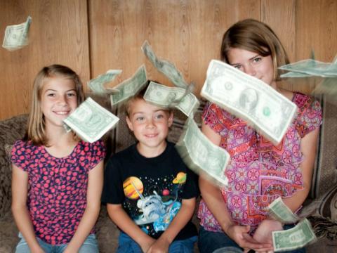 Varios niños lanzan billetes al aire