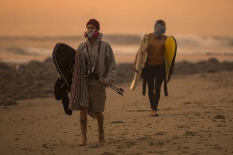 Un cielo lleno de humo filtra la luz del atardecer alrededor de los surfistas mientras el Thomas Fire  crece y amenaza a la población entre Carpinteria  y Santa Bárbara el 12 de diciembre de 2017 en Carpinteria (California, EE.UU.).