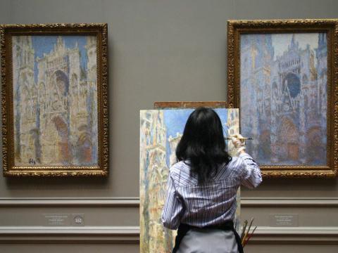 Una persona pinta un cuadro dentro de un museo