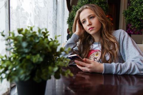 Una niña triste con el móvil