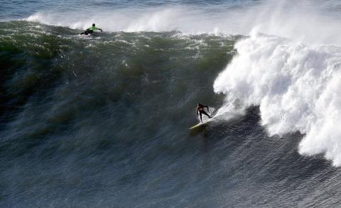El surfista Adrián Fernández De Valderrama (d) realiza un take off, siendo segundo en final por detrás del californiano Nick Lamb (i)