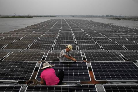 Los trabajadores preparan las placas en el huerto solar chino.